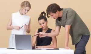Team of people gathered around laptop.